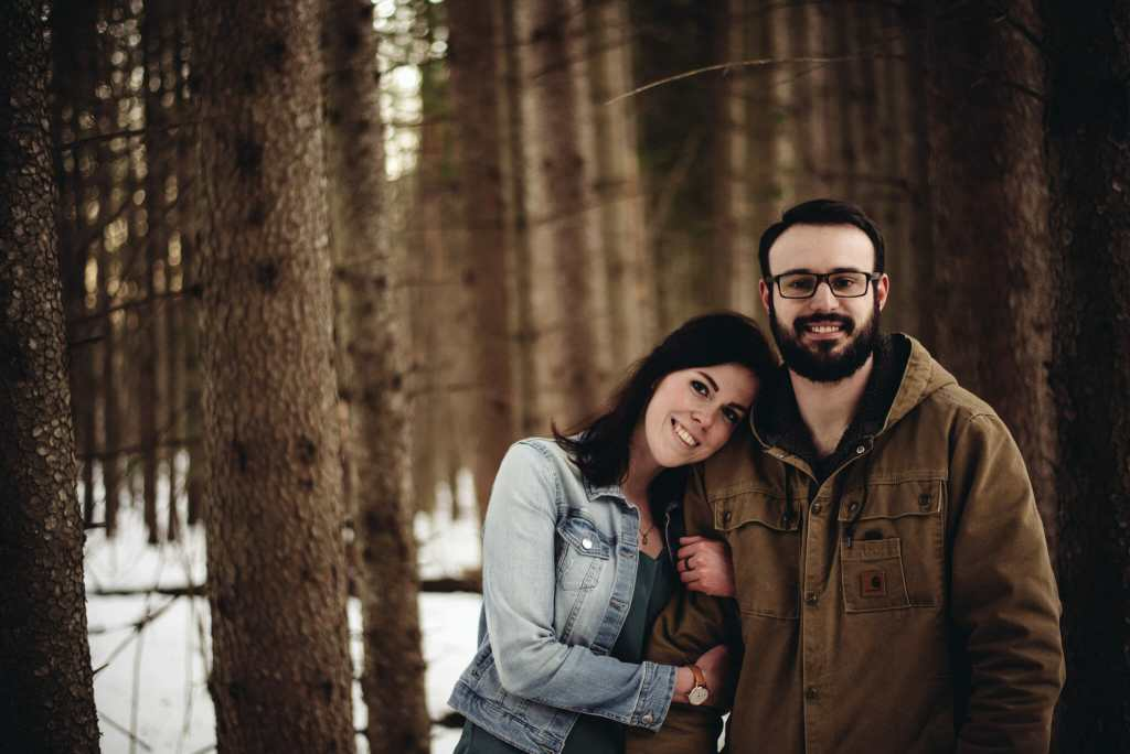 couple cuddles in trees at conservation area