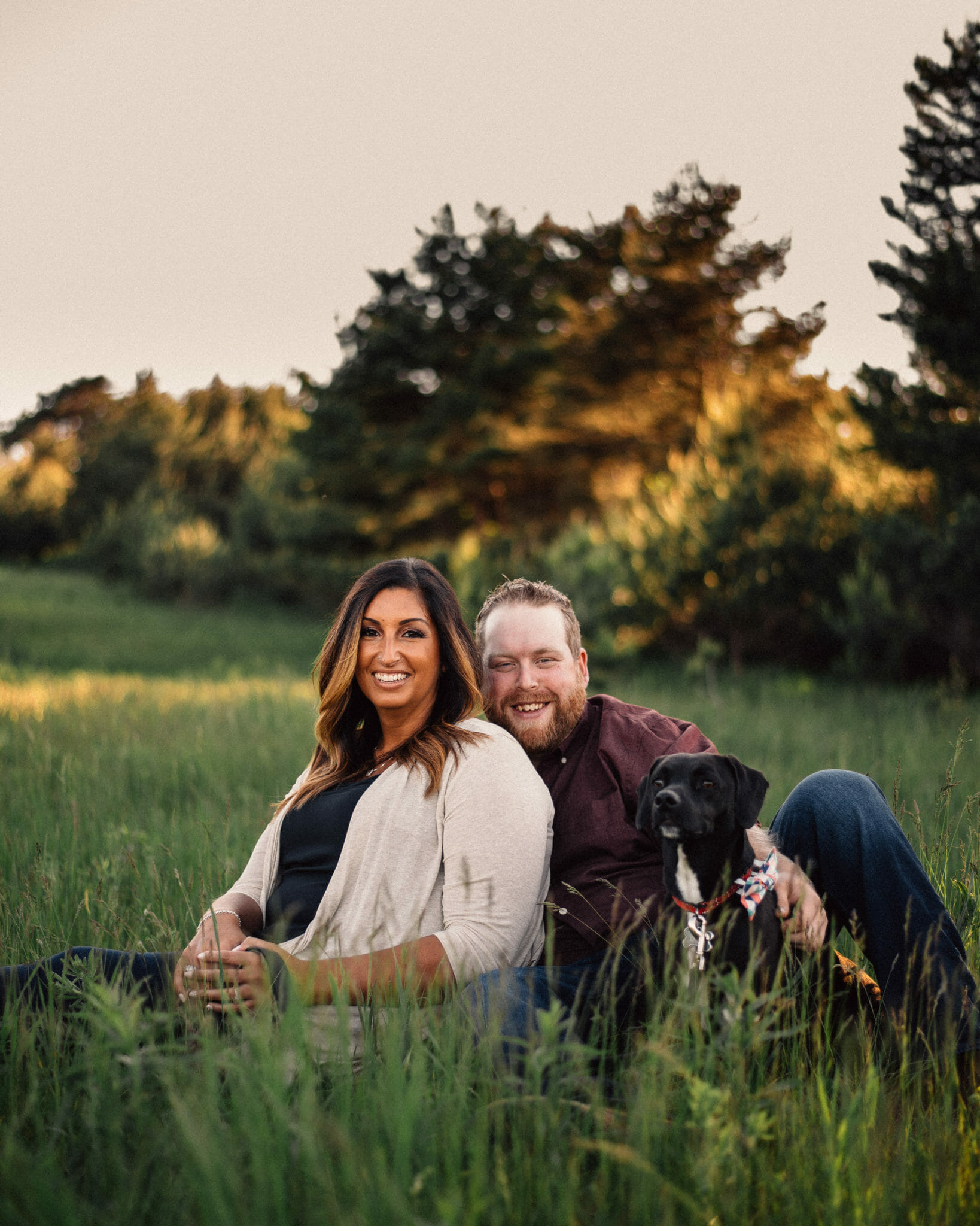 couple sit in tall grass during photo shoot