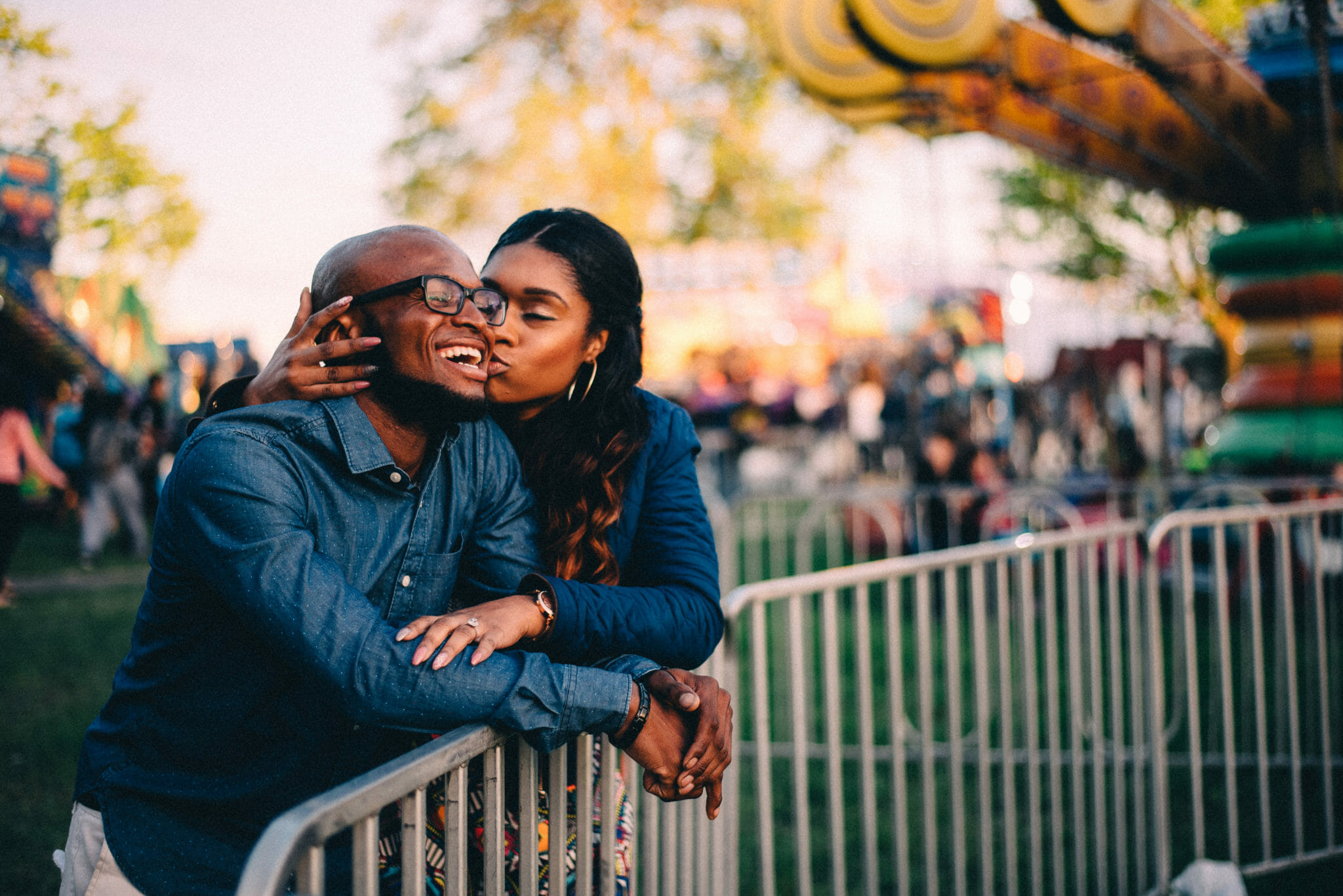 engaged couple kisses at carnival