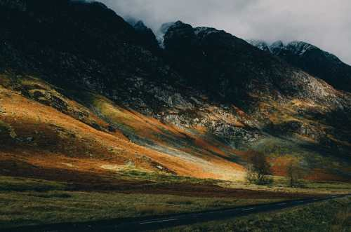 sun light hits the munros of glencoe scotland