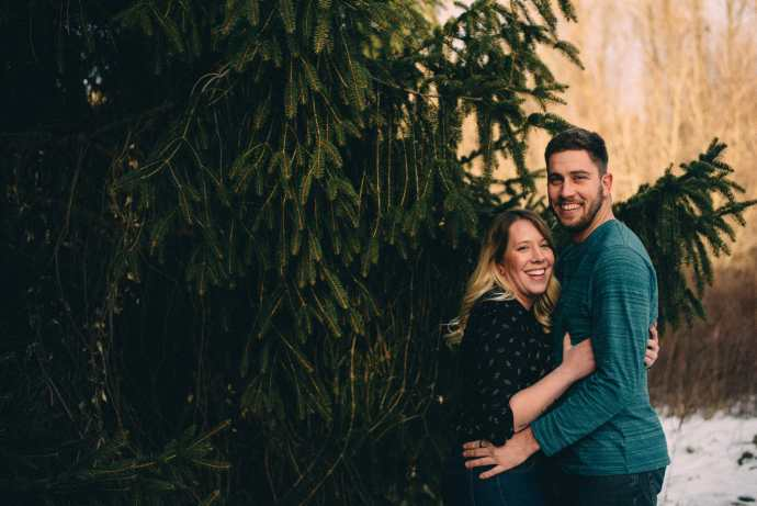 couple embraces by pine tree conservation area