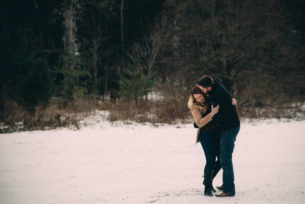 engaged couple cuddle in snowy field heber down