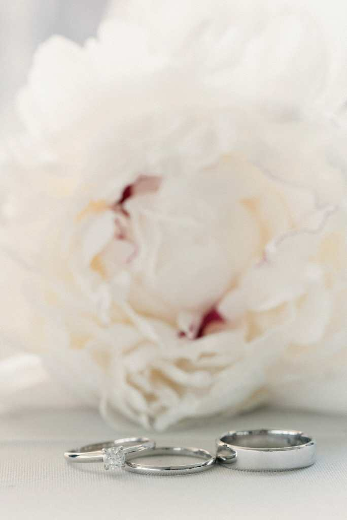 wedding ring shot in front of white flower
