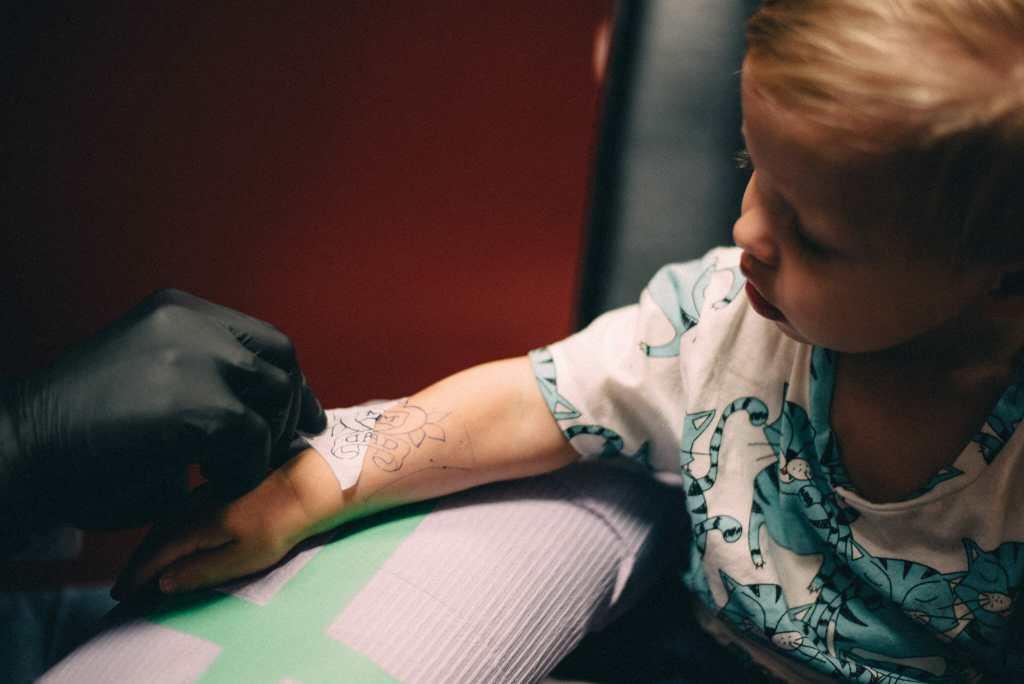 little boy gets mom and dad stencil tattoo
