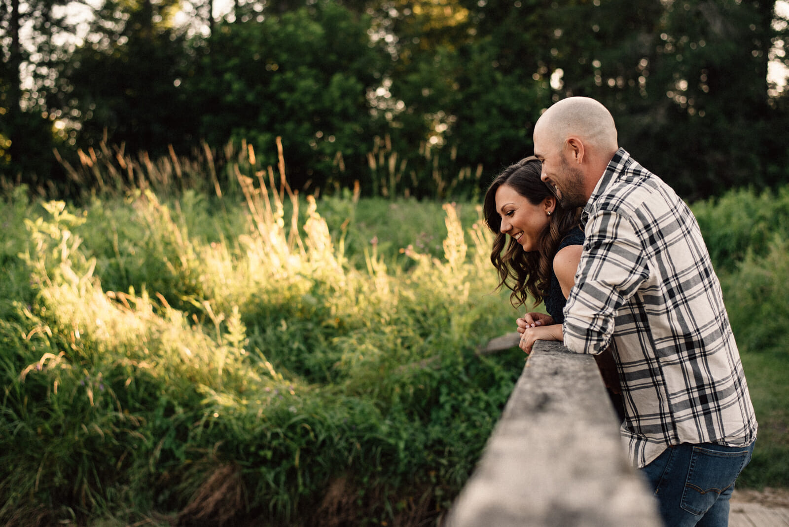engaged couple laugh and look over bridge in alliston