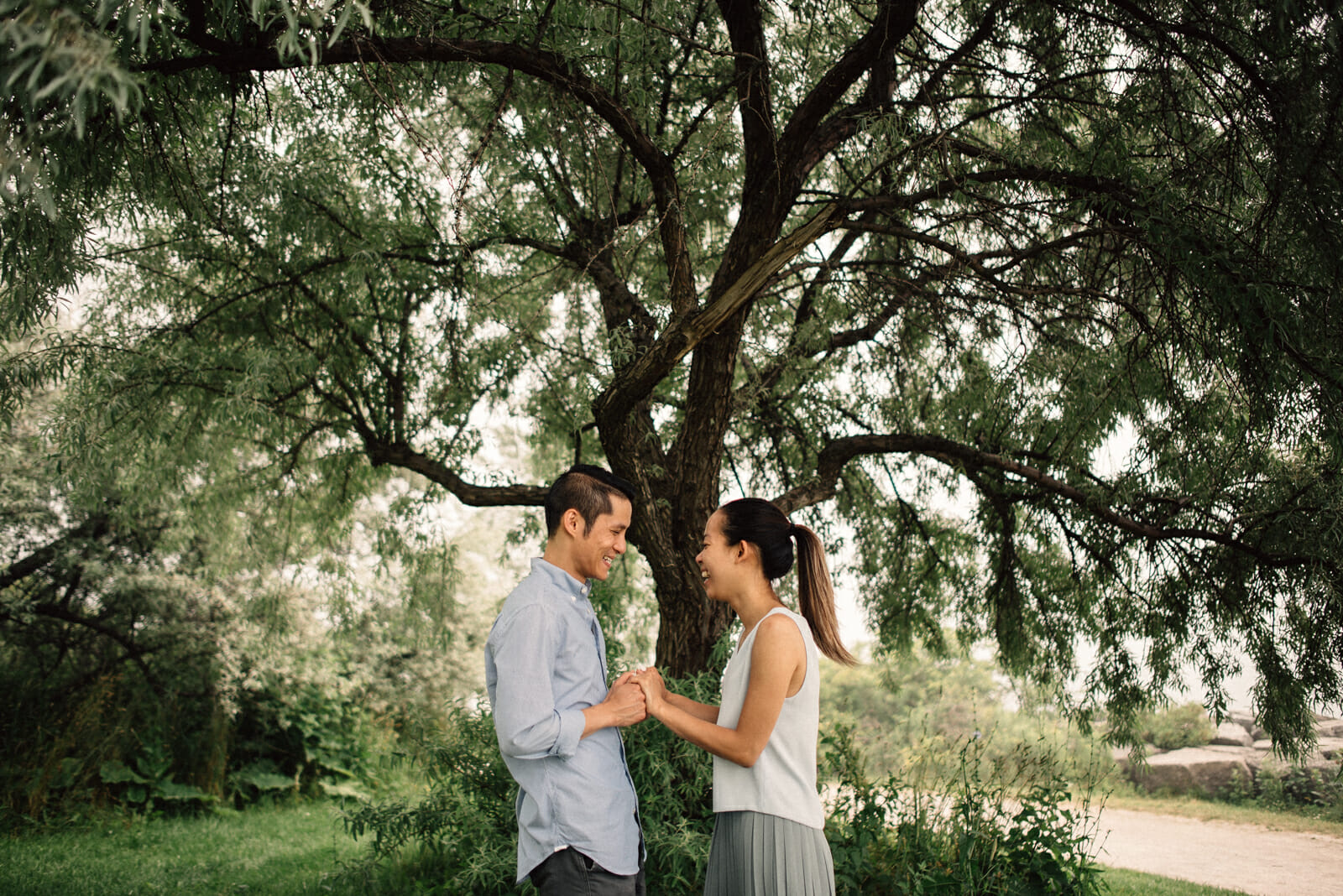 couple laughs under tree while holding hands