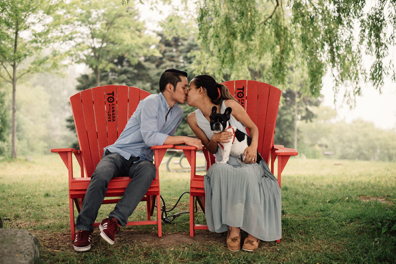 couple kisses while sitting on muskoka chairs at beach