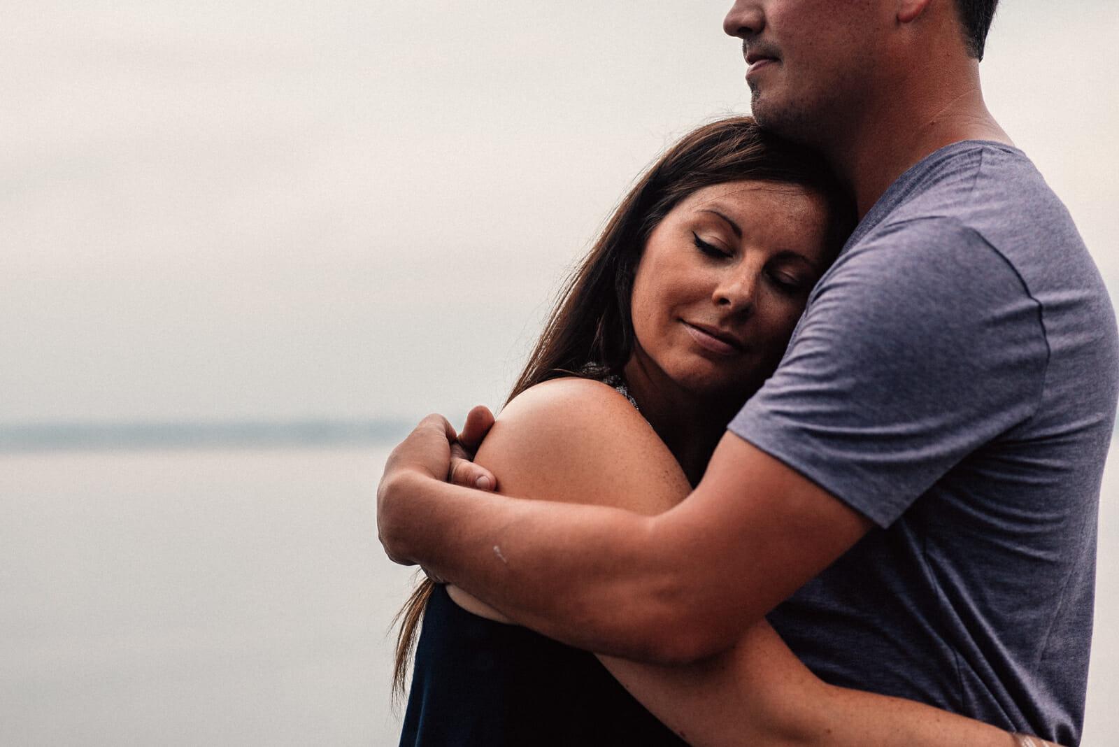 engaged couple cuddle on lake simcoe dock
