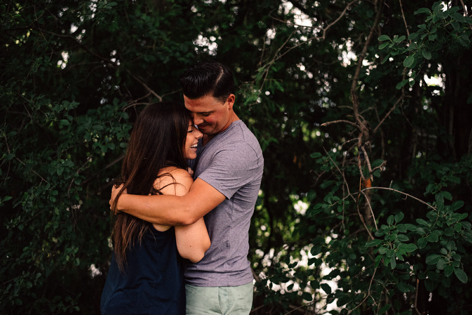 husband and wife hug and laugh in forest