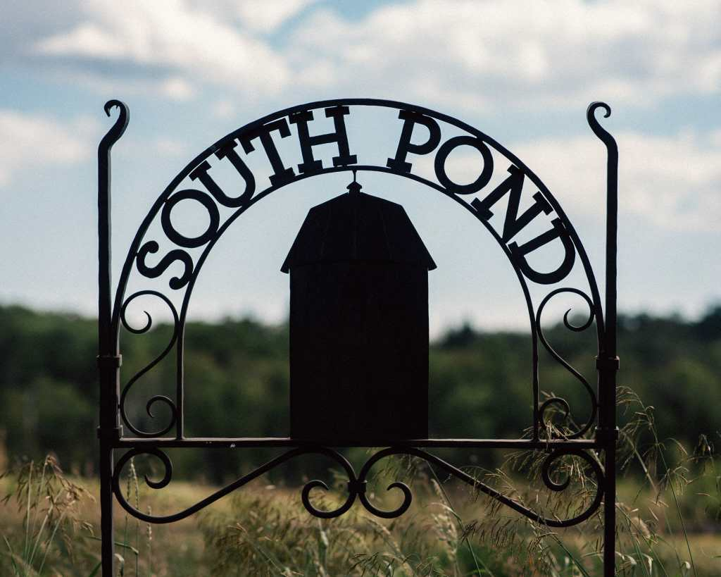 south pond farms sign with farmers field