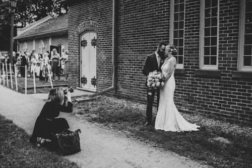 chelsey cunningham photographing bride and groom in front of enoch turner schoolhouse