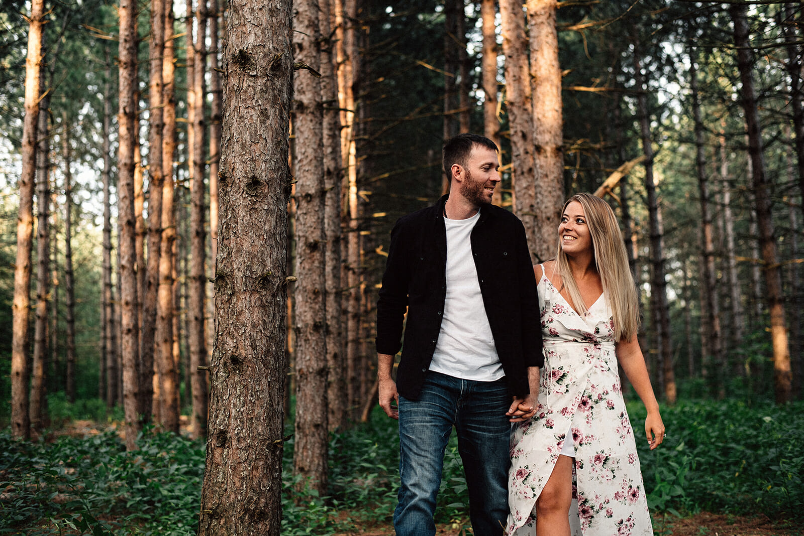 engaged couple walks through the trees holding hands
