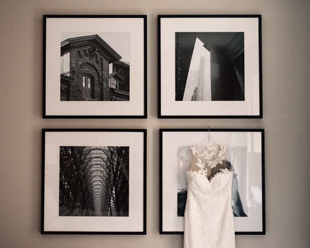 wedding dress hangs on printed photos of toronto