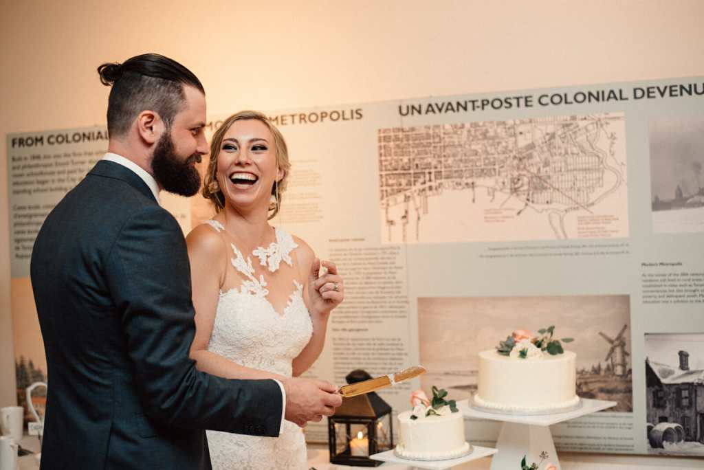 bride and groom laugh during the cutting of their wedding cake