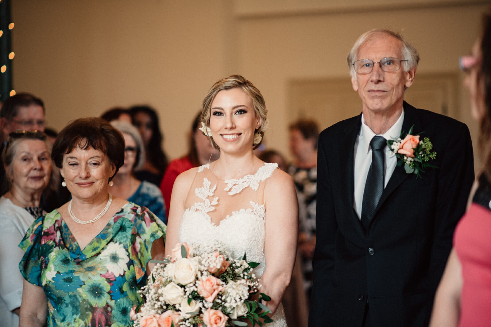 mother and father walk bride down the aisle