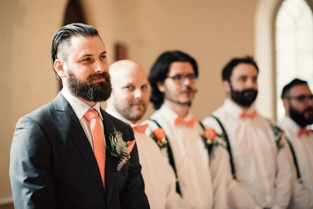 groom looks on as his bride walks down the aisle