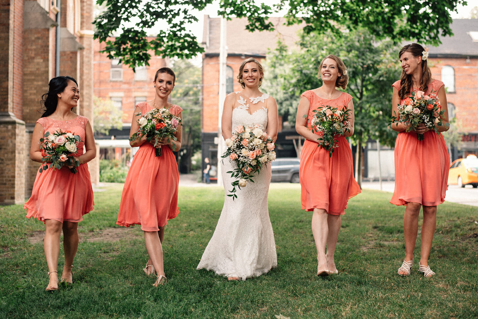 bride walks with bridesmaids by church in toronto