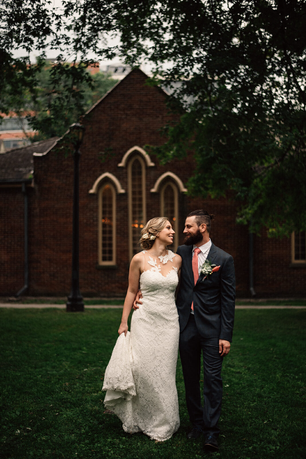 bride and groom walk in parkette between little trinity church and enoch turner