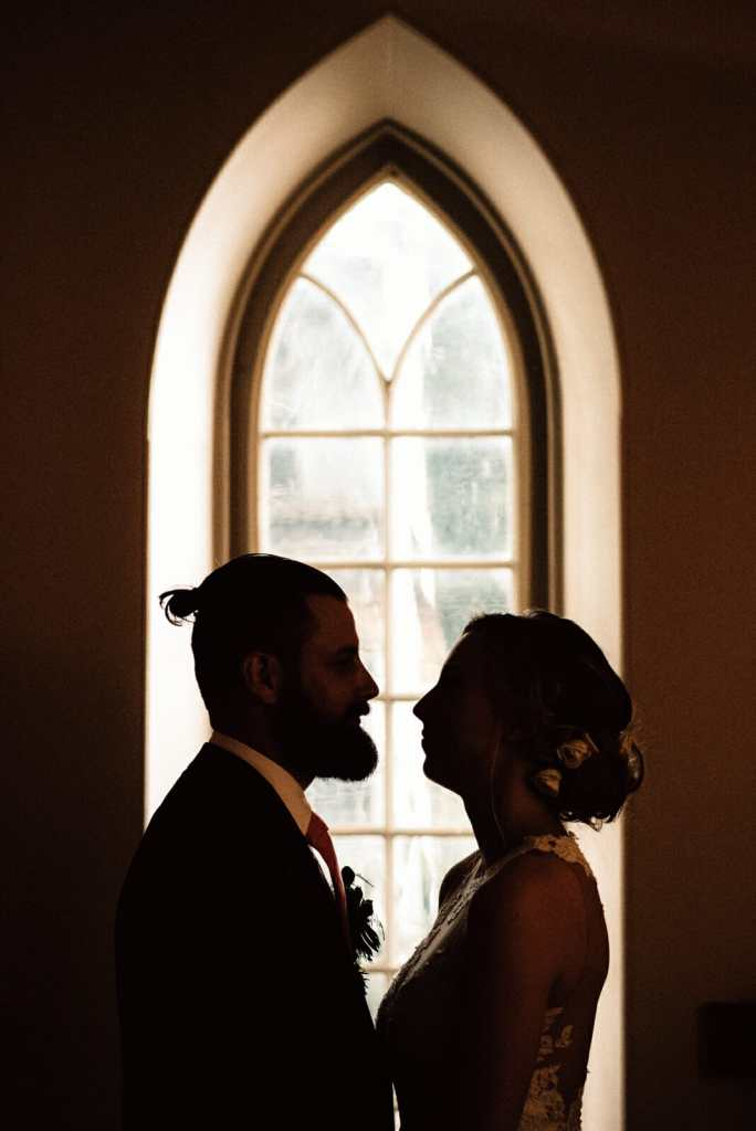 silhouette of bride and groom in front of gothic windows