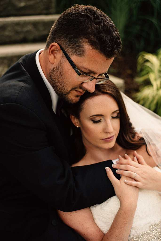 husband and wife cuddle on stairs during wedding photos