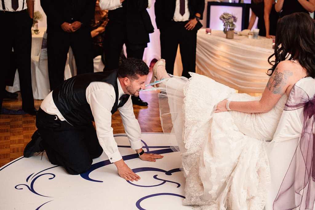 groom takes off brides garter using teeth