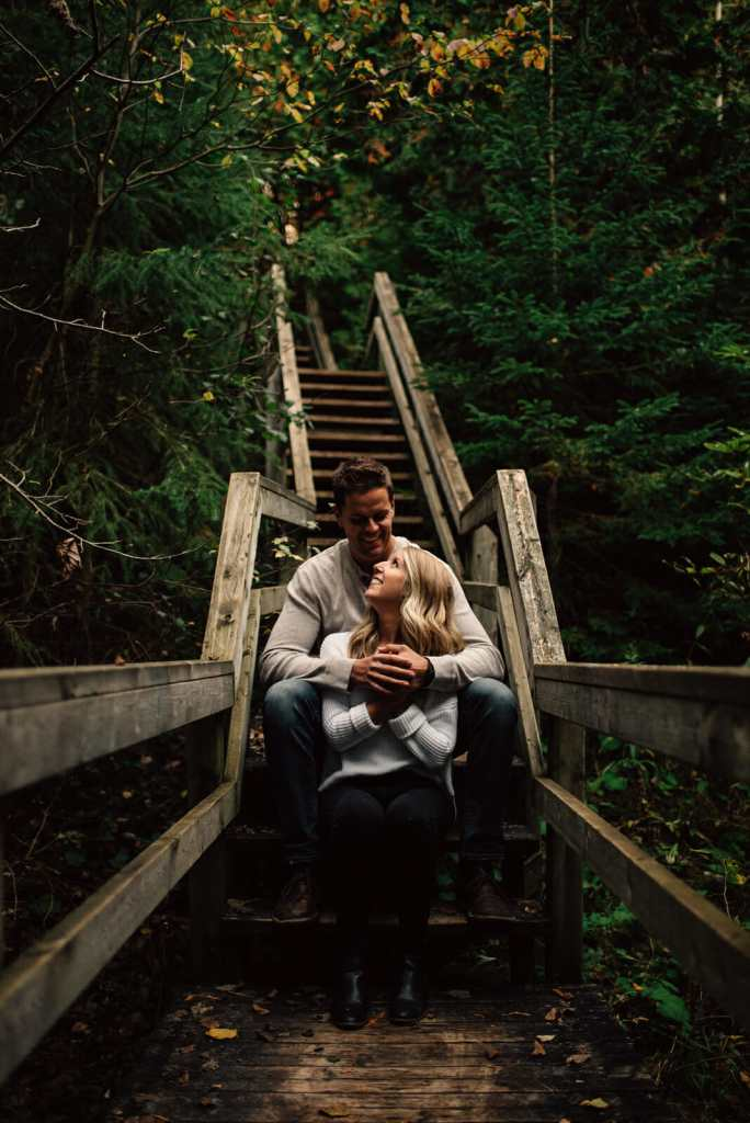 couple cuddles on stairs in forest