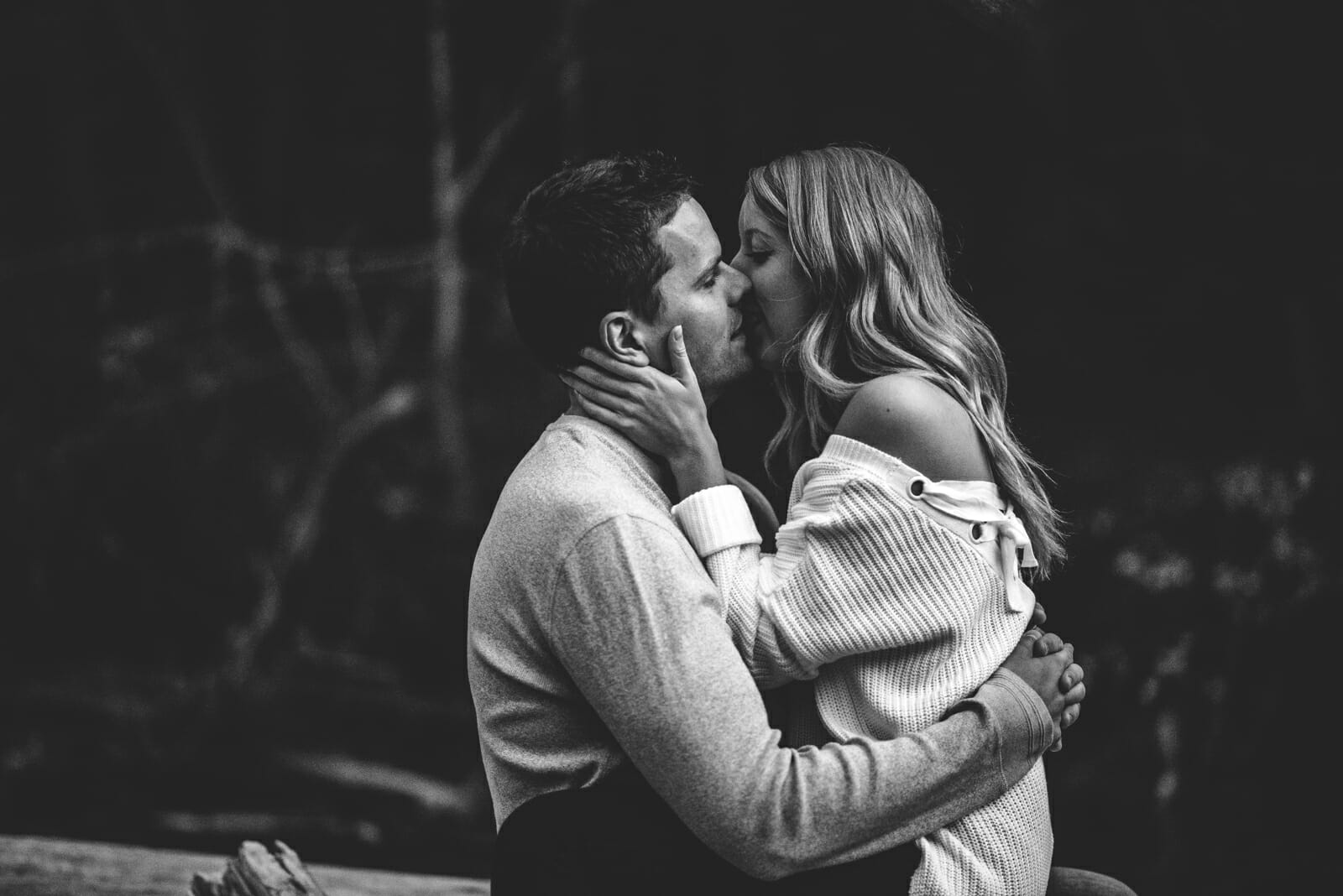 intimate kiss between couple sitting on log in forest
