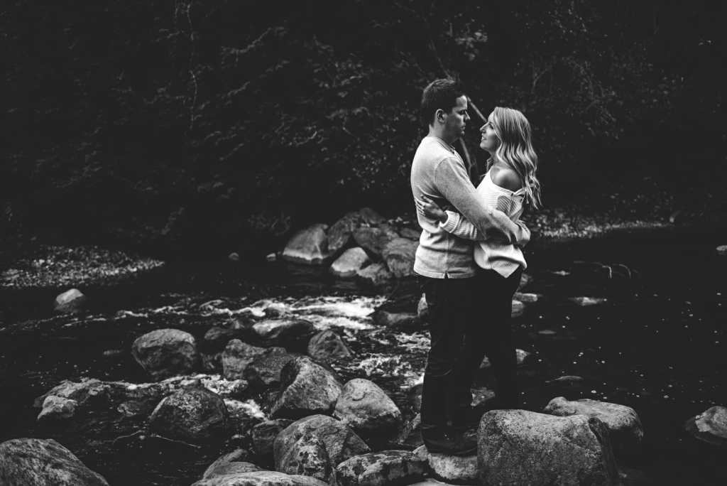 couple stands on rocks in river ontario photographer