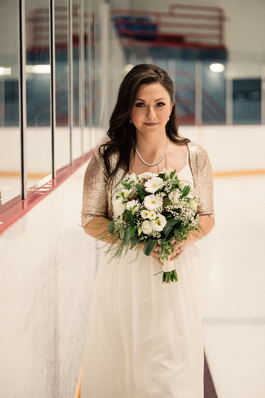 bride walks down the aisle for centre ice wedding
