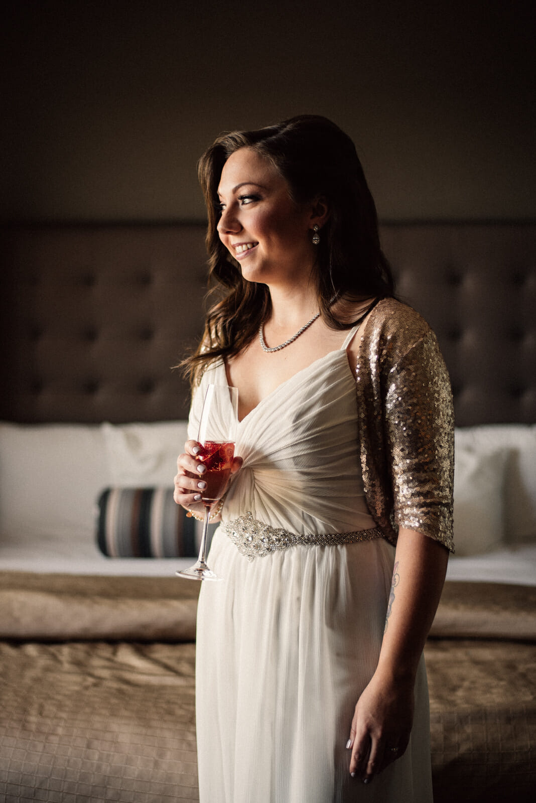 bride drinks champagne while getting ready