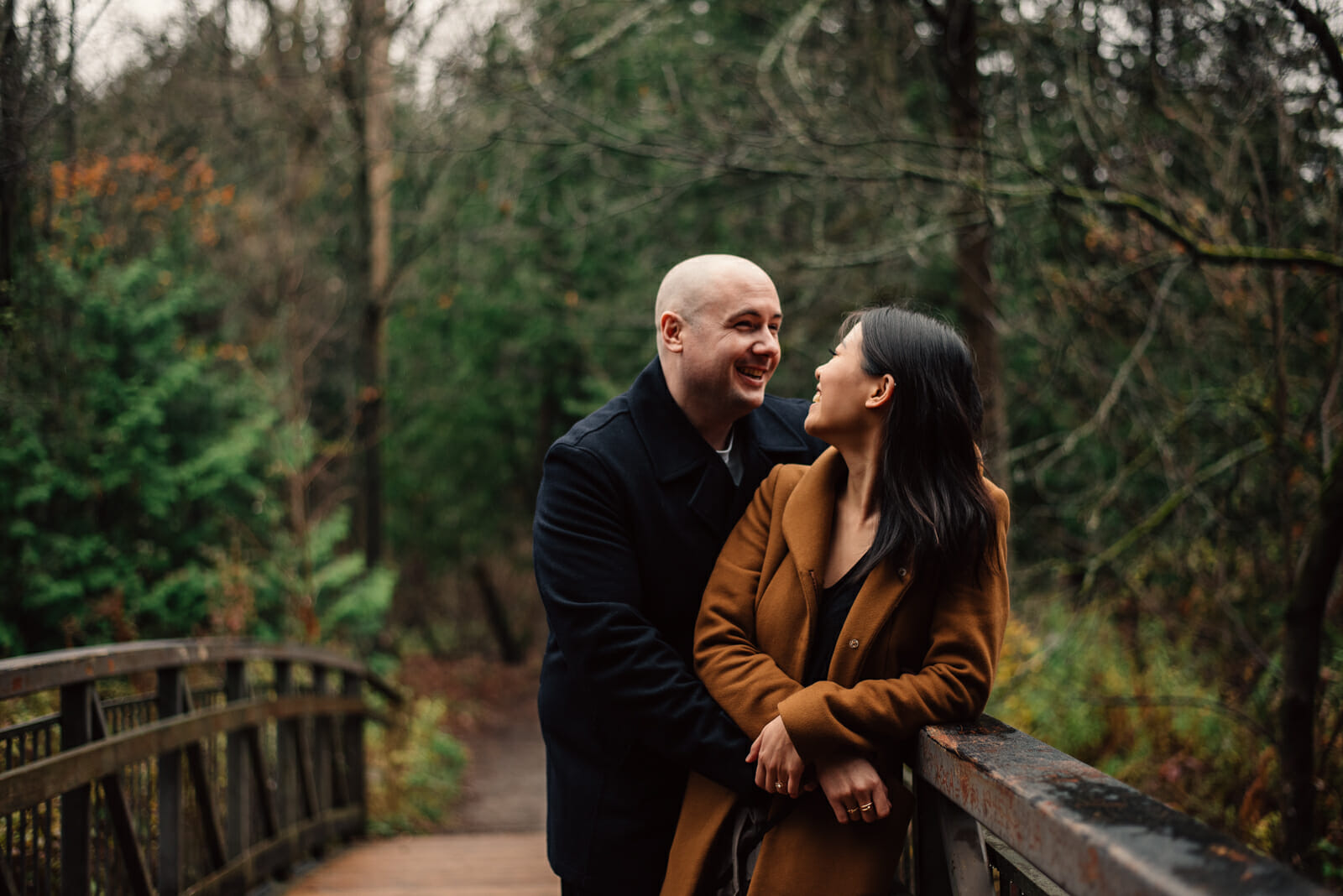 engaged couple laugh together while leaning against bridge railing