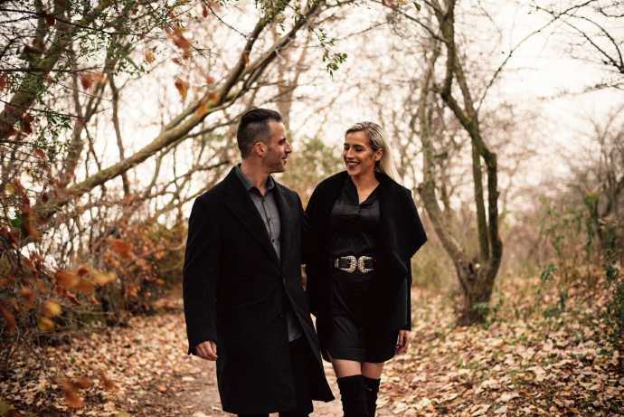 couple walks and laughs on forest trail at woodbine park in toronto