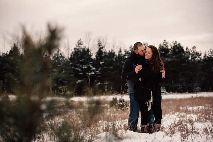 engaged couple cuddle in snowy field
