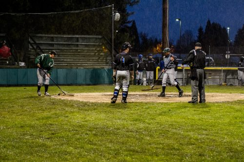 Troy Benton (left), a freshman pitcher, and head coach Nathan Pratt spread Turface around home plate. Turface soaks up water and mud, that dries the ground out a little quickly to resume play. As Lane's catcher and umpire standby watching them work during thursday night's second game.