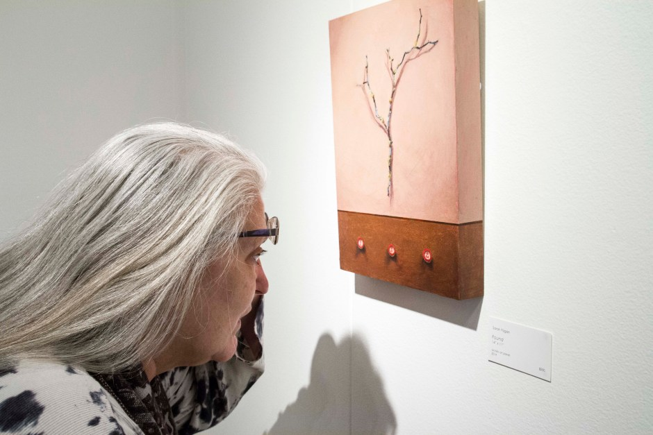 """Michelle FitzHenry closely examines the bingo buttons in Sarah Fagan's painting """"Found"""" in the Chemeketa Art Gallery."""