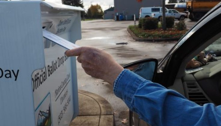 An Oregon resident drops off his ballot at an official ballot drop box. Photos by Saul Rodriguez