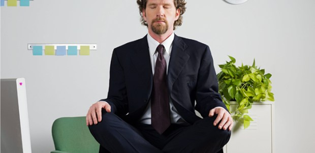 Businessman meditating on desk