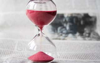 An hour glass with red sands flowing to indicate time passing