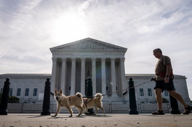 Supreme Court, with a man waking his dogs in front of it