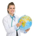 Female practitioner with Stethoscope on a globe of the world for our masters in global medicine seminars