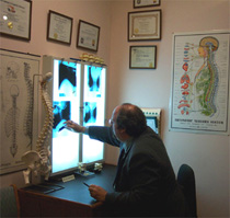 Dr Ron Cherubino, creator of the cherubhealth healing system, evaluating xrays on viewbox at Cherubino Health Center
