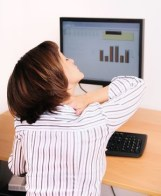 Photograph of a woman working at a computer holding her neck and shoulder