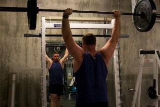 Kevin works out in the gym in the basement of the police station several nights a week before going on duty. As required for K-9 patrol teams, Kevin must be able to lift 87-pound Baron over fences or other obstacles when tracking fleeing suspects.