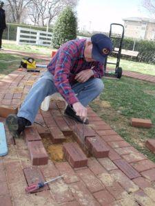 Photo by Tony Pasek. Hobie installs memorial bricks on walkway.