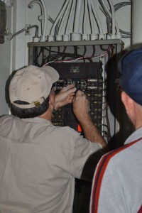 Photo by Anne Puppa Greg and Hobie work on electrical penal.