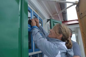 Lindsey Goodison removing tape after painting window frames.