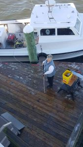 Cathy and Howard power wash the dock.