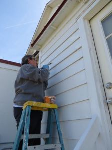 Carolyn touches up paint job on Keeper's house.
