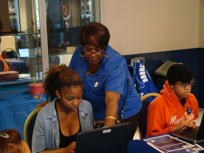 Mrs. Amerson helping a student with the online survey in the Student Center
