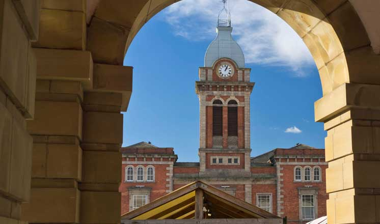 The clock tower of the Market Hall in Chesterfield viewed through an archway. The tops of market stalls are visible in the foreground.